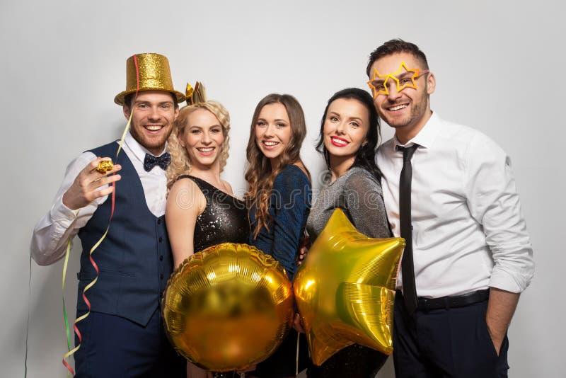 Amigos felizes com levantamento dourado dos suportes do partido fotos de stock royalty free