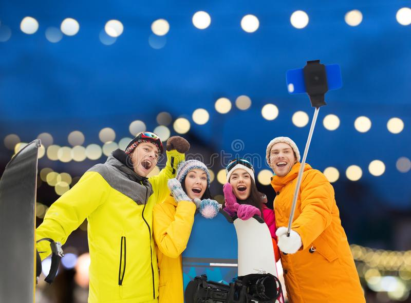 Amigos felizes com snowboards e smartphone imagens de stock royalty free