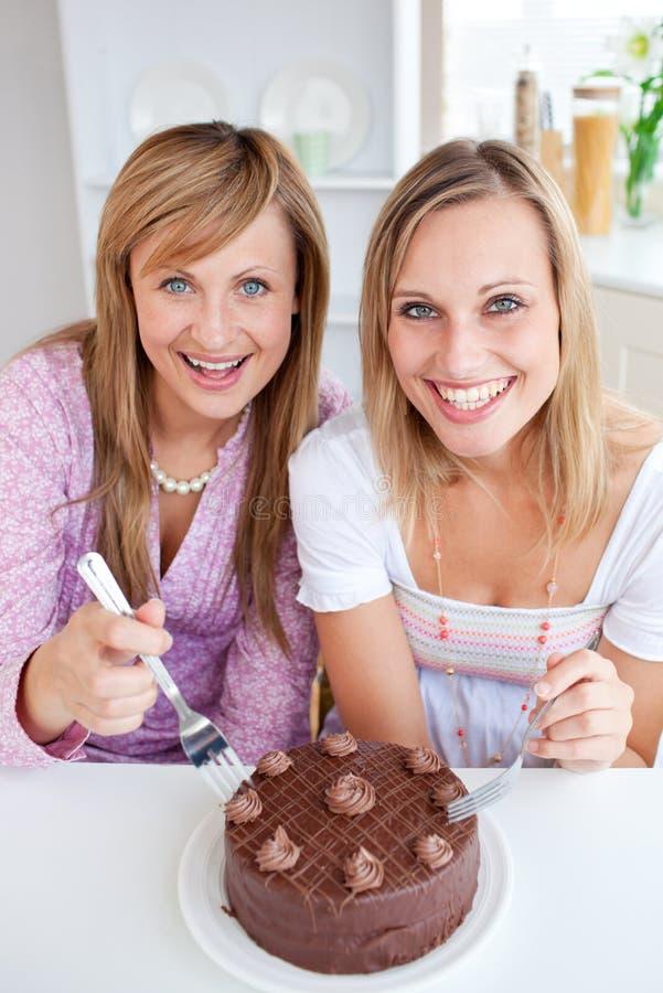 Amigos felizes com um bolo que sorriem na câmera fotografia de stock