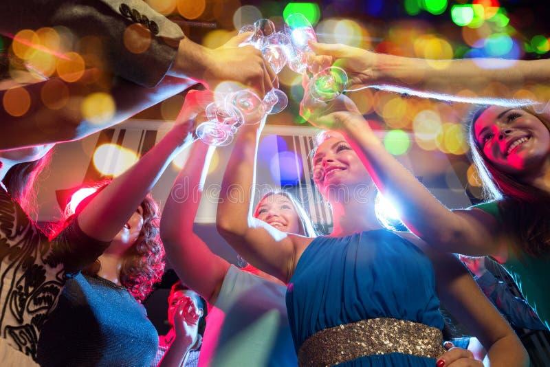 Amigos felizes com vidros do champanhe no clube fotografia de stock