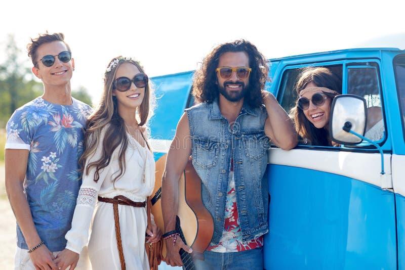 Amigos felizes da hippie com a guitarra sobre o carro da carrinha foto de stock royalty free
