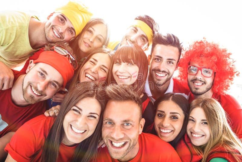 Amigos felizes do esporte que tomam o selfie no evento do futebol do mundo - amigo fotografia de stock