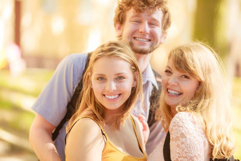 Amigos felizes dos jovens exteriores imagens de stock