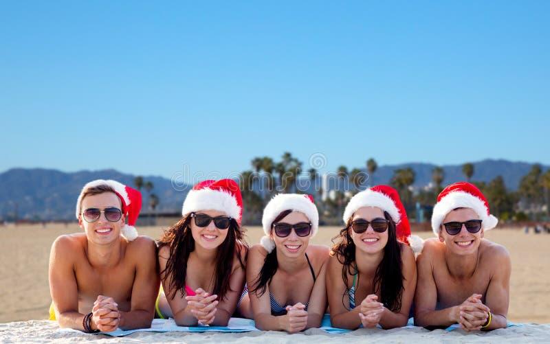 Amigos felizes em chapéus de Santa na praia no Natal imagem de stock royalty free