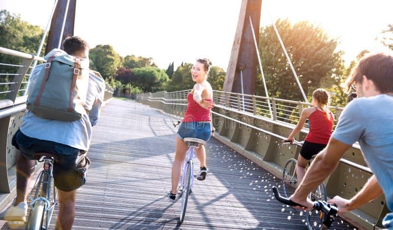 Amigos felizes milenares tendo a bicicleta da equitação do divertimento no parque da cidade - conceito da amizade com biking mill foto de stock