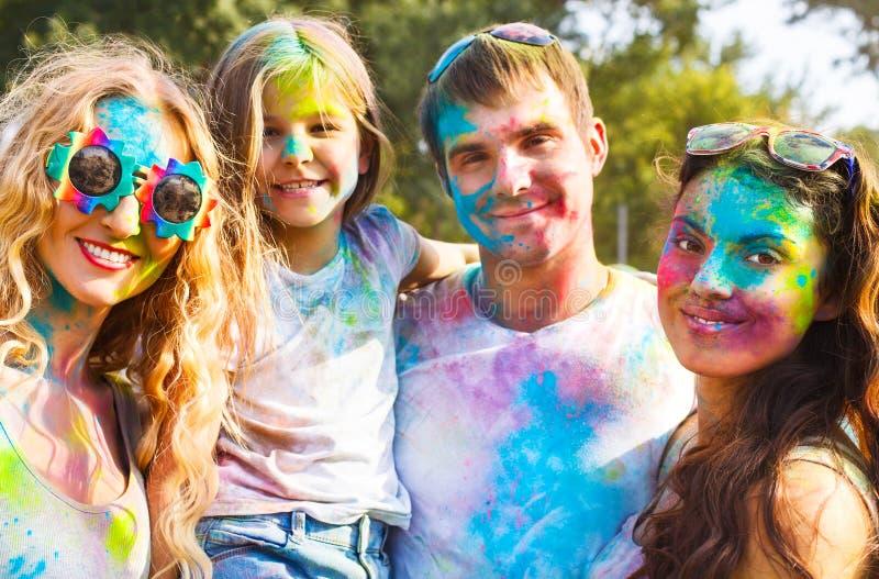 Amigos felizes no festival da cor do holi foto de stock