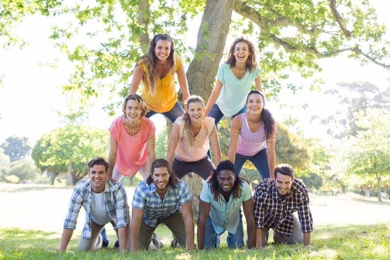 Amigos felizes no parque que faz a pirâmide humana foto de stock royalty free