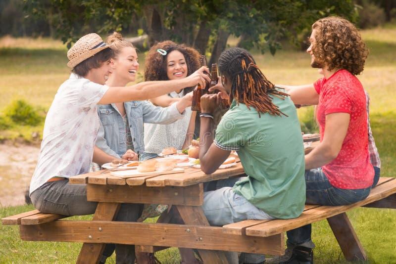 Amigos felizes no parque que tem o almoço imagens de stock