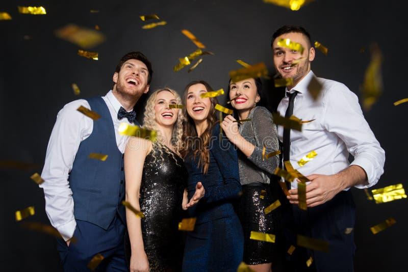 Amigos felizes no partido sob confetes sobre o preto foto de stock royalty free