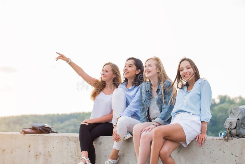 Amigos felizes no piquenique fora Povos de sorriso novos que sentam-se na beira concreta e uma na menina que apontam acima foto de stock royalty free