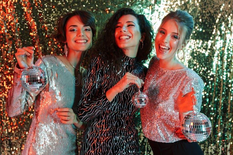Amigos felizes novos bonitos das mulheres que levantam sobre o fundo da parede do brilho que guarda mini bolas pequenas do disco  fotografia de stock royalty free