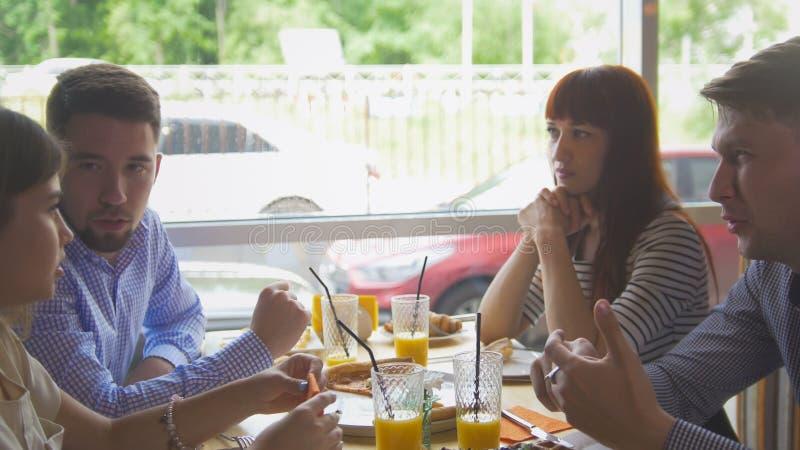 Amigos felizes novos que apreciam um jantar e que penduram para fora no restaurante imagem de stock