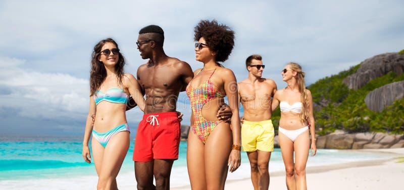 Amigos felizes que andam ao longo da praia do ver?o imagens de stock