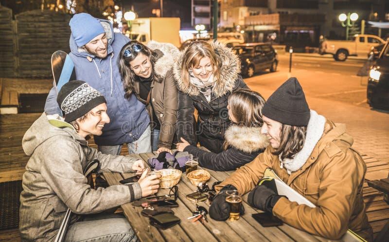 Amigos felizes que bebem a cerveja e que comem microplaquetas após na barra do esqui fotografia de stock royalty free