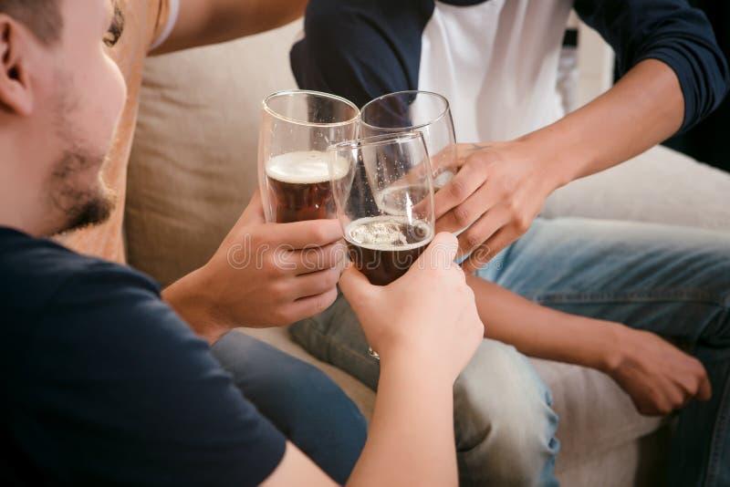 Amigos felizes que bebem a cerveja em casa imagem de stock