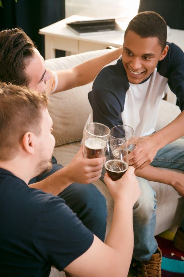 Amigos felizes que bebem a cerveja em casa fotografia de stock royalty free