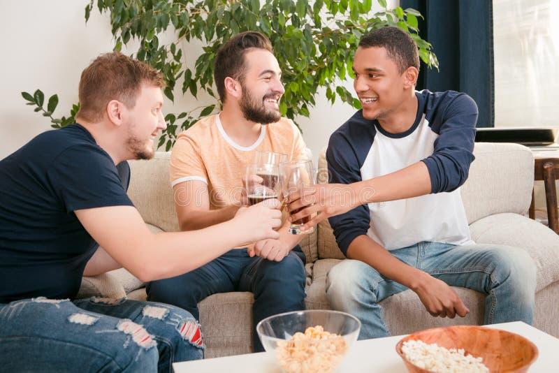 Amigos felizes que bebem a cerveja em casa imagens de stock royalty free
