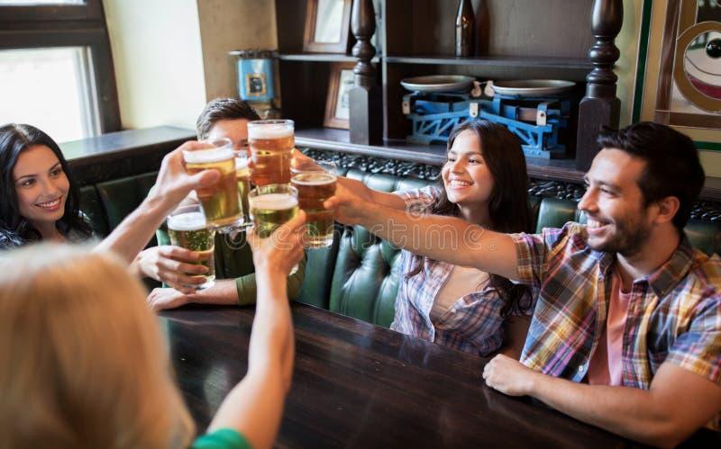 Amigos felizes que bebem a cerveja na barra ou no bar foto de stock royalty free