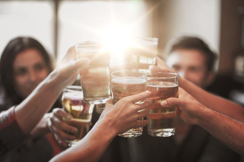 Amigos felizes que bebem a cerveja na barra ou no bar fotografia de stock royalty free