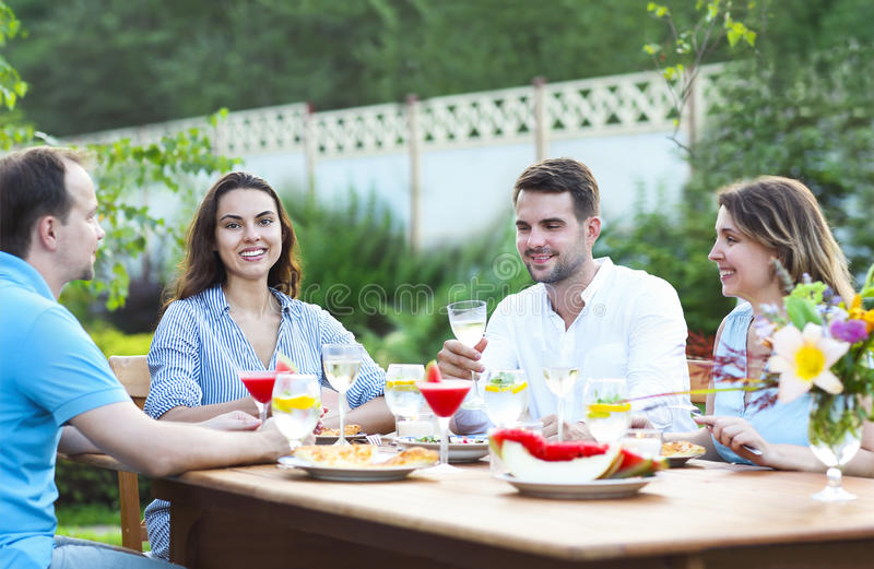 Amigos felizes que brindam vidros de vinho no jardim ao ter l fotos de stock