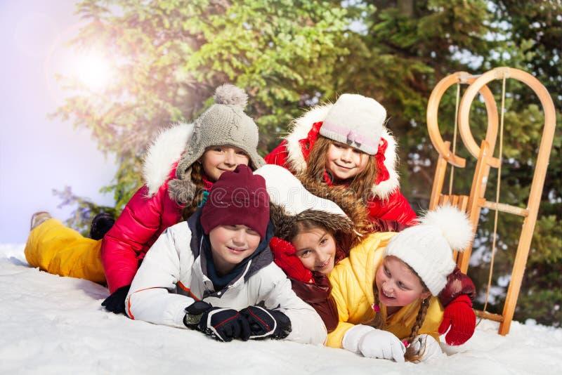 Amigos felizes que colocam na neve na floresta do inverno imagem de stock royalty free