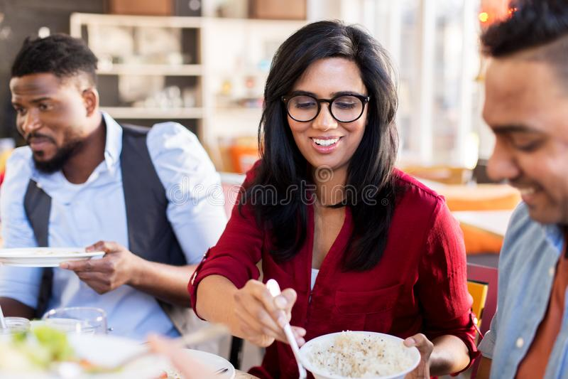 Amigos felizes que comem no restaurante fotografia de stock
