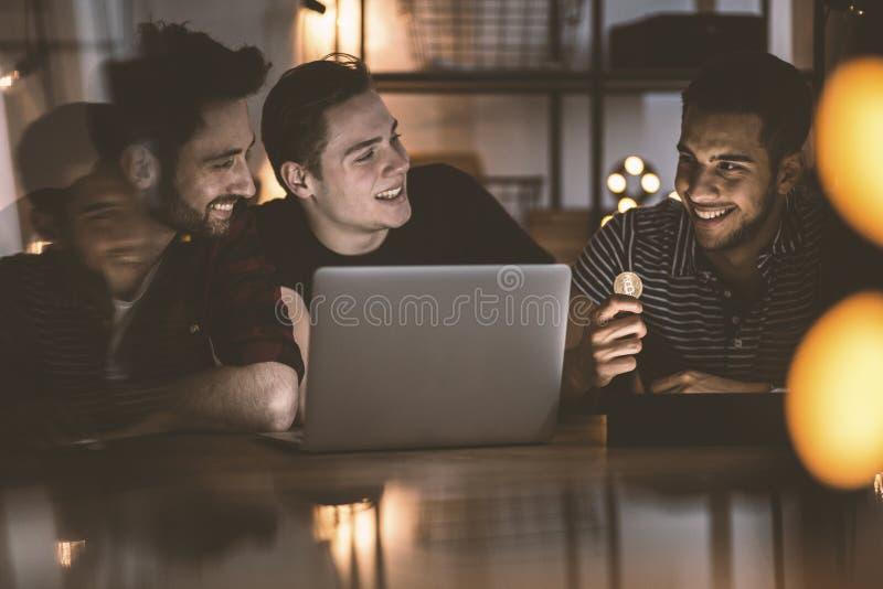 Amigos felizes que compram o dinheiro digital e que olham o filme no portátil foto de stock royalty free