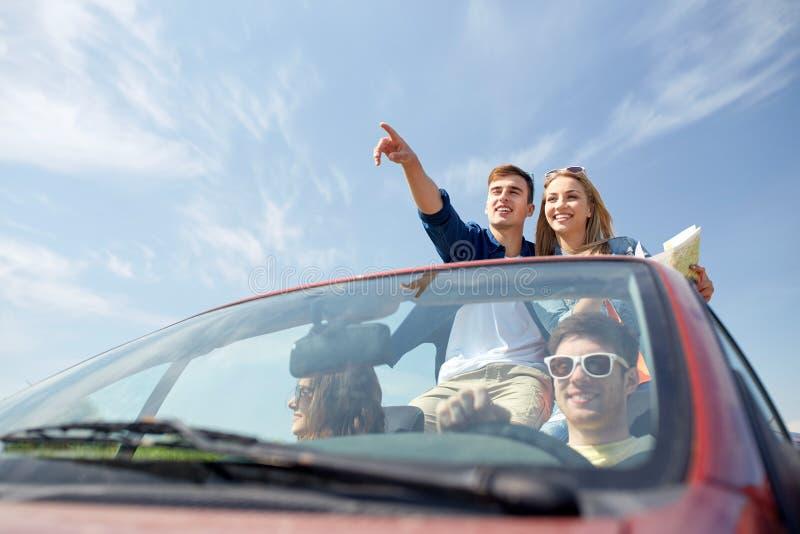 Amigos felizes que conduzem no carro do cabriolet imagem de stock
