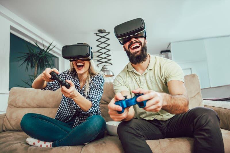 Amigos felizes que jogam jogos de vídeo com vidros da realidade virtual imagens de stock