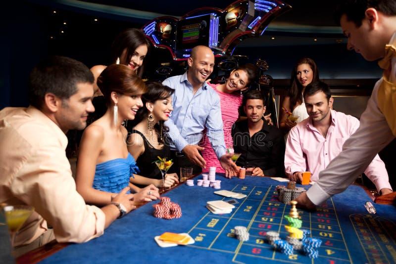 Amigos felizes que jogam a roleta em um casino fotografia de stock royalty free