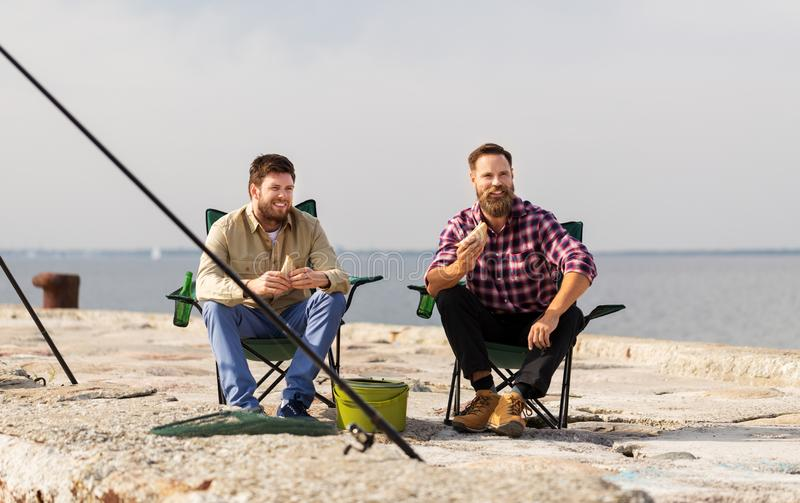 Amigos felizes que pescam e que comem sandu?ches foto de stock royalty free