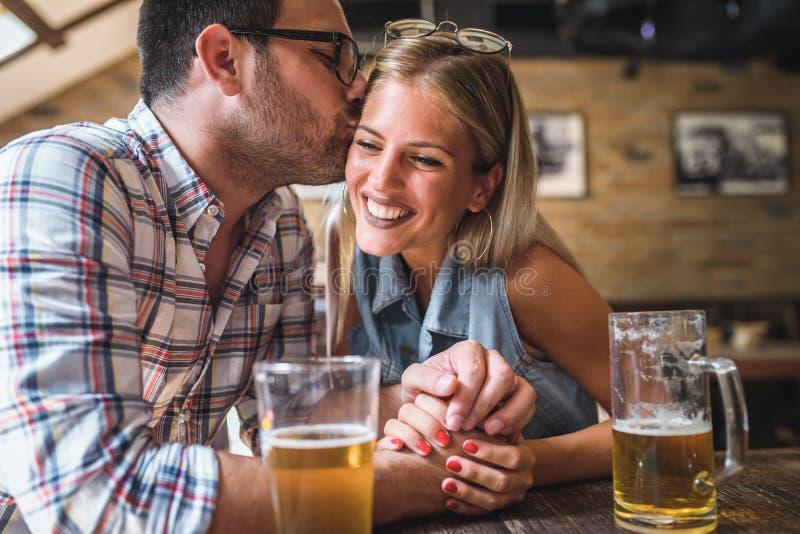 Amigos felizes que têm o divertimento na barra - cerveja bebendo dos pares na moda novos e que riem junto fotos de stock royalty free