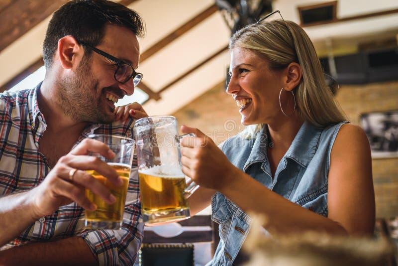 Amigos felizes que têm o divertimento na barra - cerveja bebendo dos pares na moda novos e que riem junto fotografia de stock royalty free