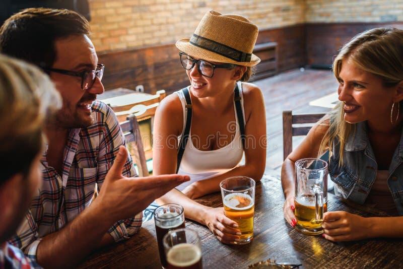 Amigos felizes que têm o divertimento na barra - cerveja bebendo dos povos na moda novos e que riem junto imagem de stock royalty free