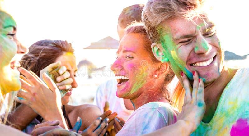 Amigos felizes que têm o divertimento no partido no evento do festival das cores do holi - jovem da praia que ri junto com o humo fotos de stock royalty free