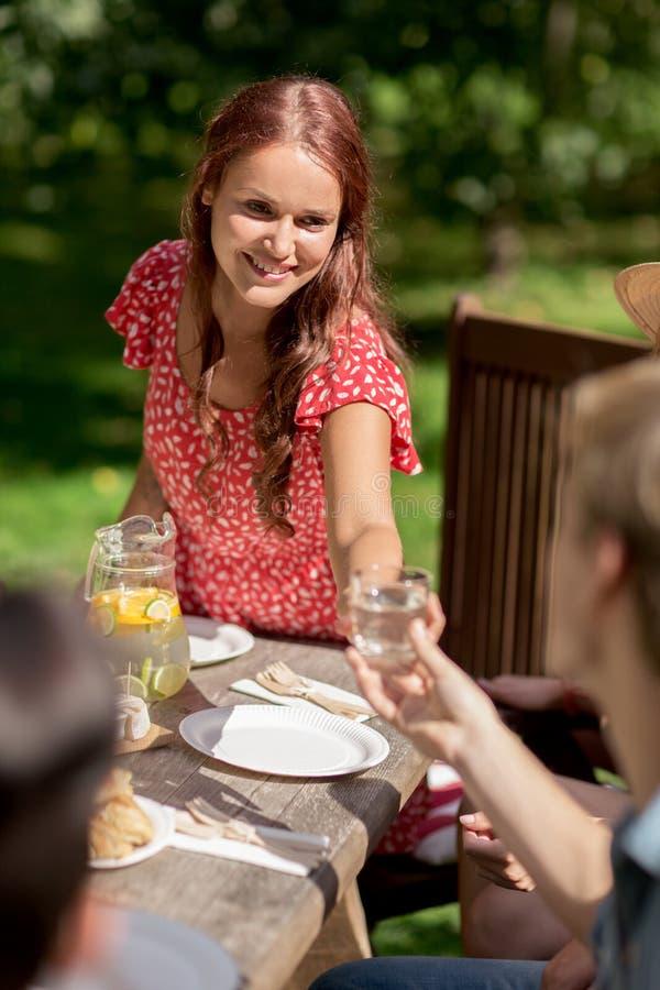 Amigos felizes que têm o jantar no partido de jardim do verão imagem de stock royalty free