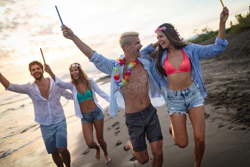 Amigos felizes que têm o partido da praia do divertimento exterior com fogos de artifício imagens de stock royalty free