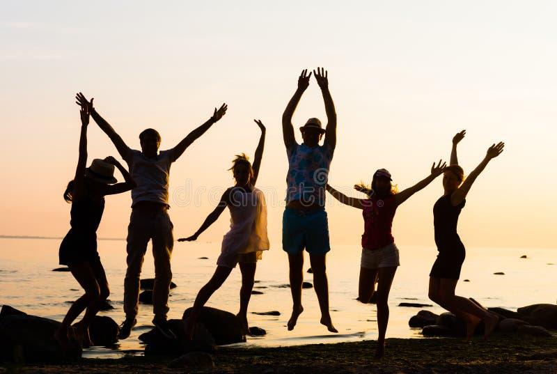 Amigos felizes que têm um partido em uma praia fotos de stock