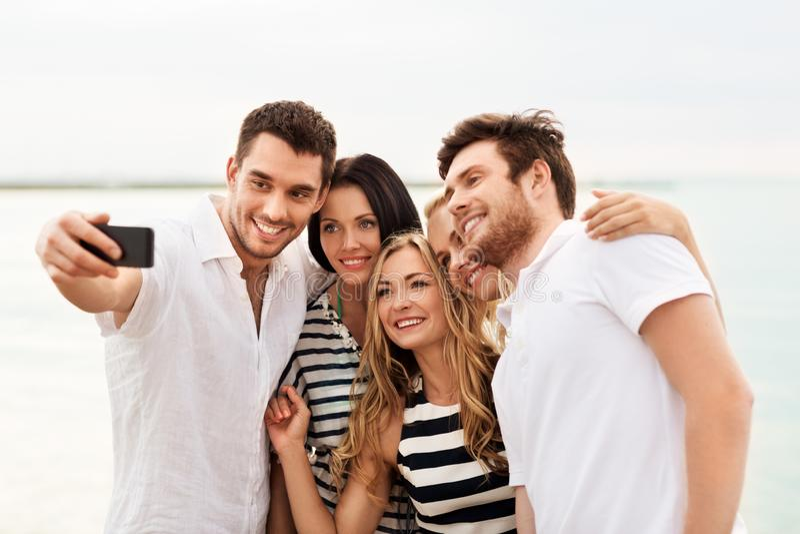 Amigos felizes que tomam o selfie na praia do verão imagens de stock royalty free