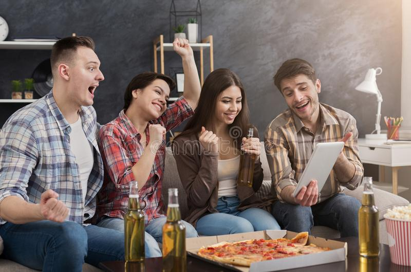 Amigos felizes que usam a tabuleta em casa fotos de stock