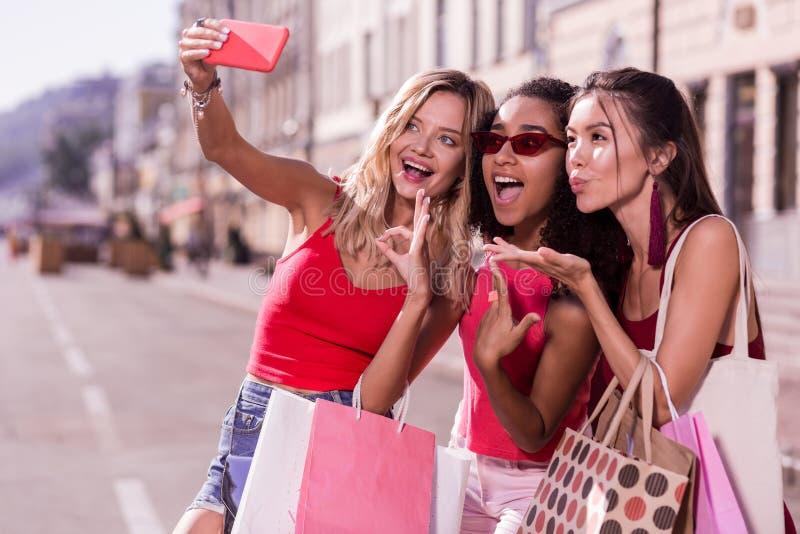 Amigos femeninos alegres felices que toman las fotos juntas imagenes de archivo