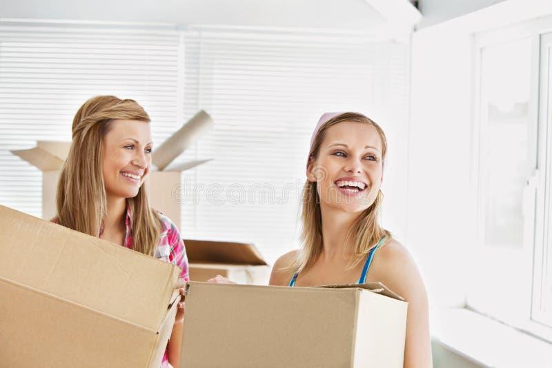 Amigos femeninos de risa que sostienen los rectángulos después de mover imagen de archivo libre de regalías