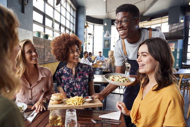 Amigos femeninos de Serving Group Of del camarero que se encuentran para las bebidas y la comida en restaurante fotografía de archivo libre de regalías