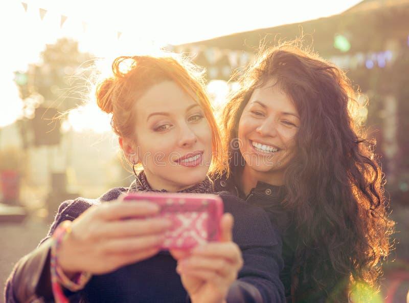 Amigos femeninos dos mujeres que toman el selfie que se divierte durante partida del fin de semana imagenes de archivo