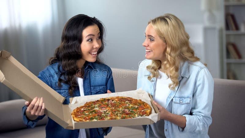 Amigos femeninos emocionados con la pizza deliciosa enorme, servicio de entrega de la comida, hogar fotografía de archivo libre de regalías