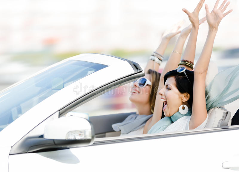 Amigos femeninos en el cabriolé con las manos para arriba fotos de archivo libres de regalías