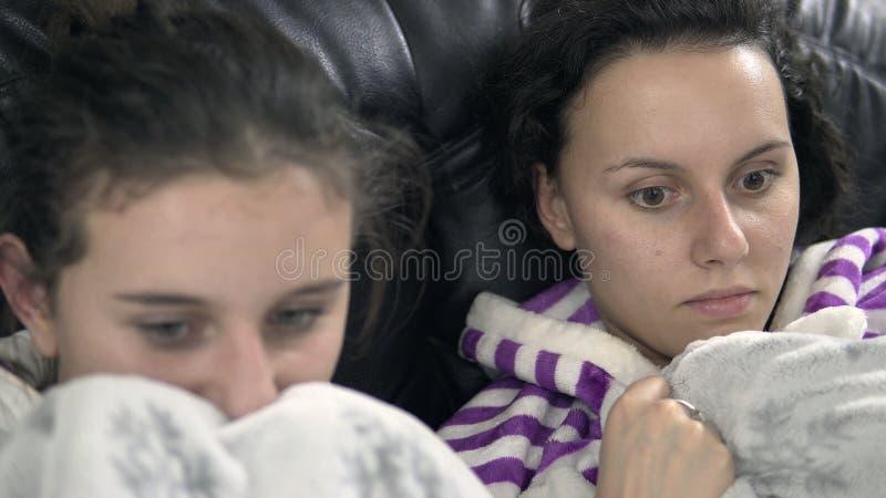 Amigos femeninos en el sofá que miran programa de televisión asustadizo fotos de archivo libres de regalías