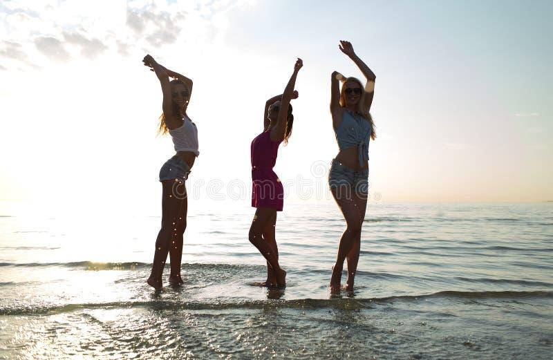 Amigos femeninos felices que bailan en la playa fotos de archivo