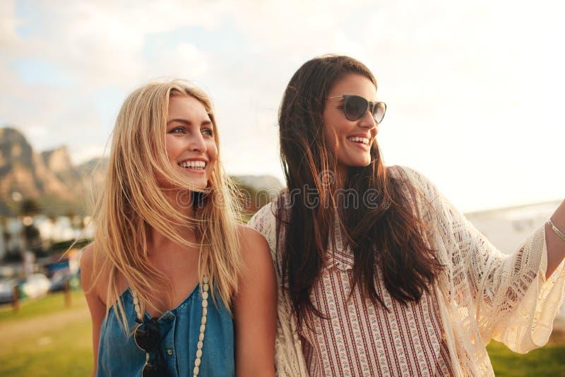 Amigos femeninos jovenes alegres junto en una playa imágenes de archivo libres de regalías