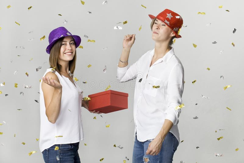 Amigos femeninos jovenes del baile feliz que sonríen con el regalo y el confeti contra el fondo blanco celebración imagenes de archivo